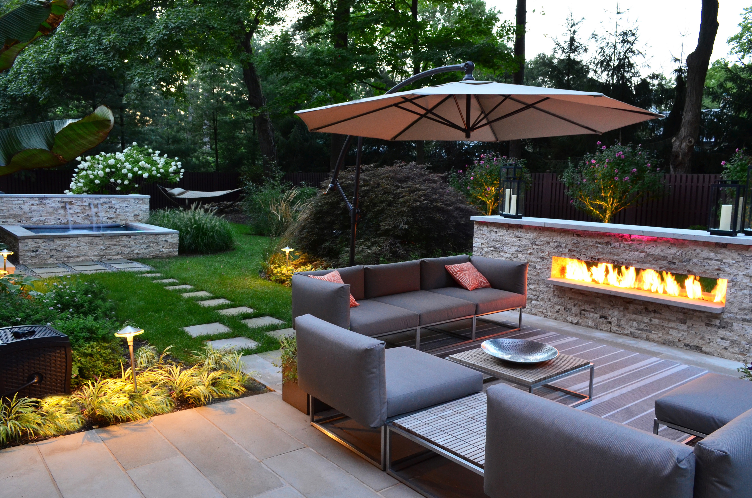 Charming-Modern-Patio-With-Gray-Stone-Outdoor-Fireplace-Also-Cream-Umbrella-As-Well-As-Beautiful-Garden