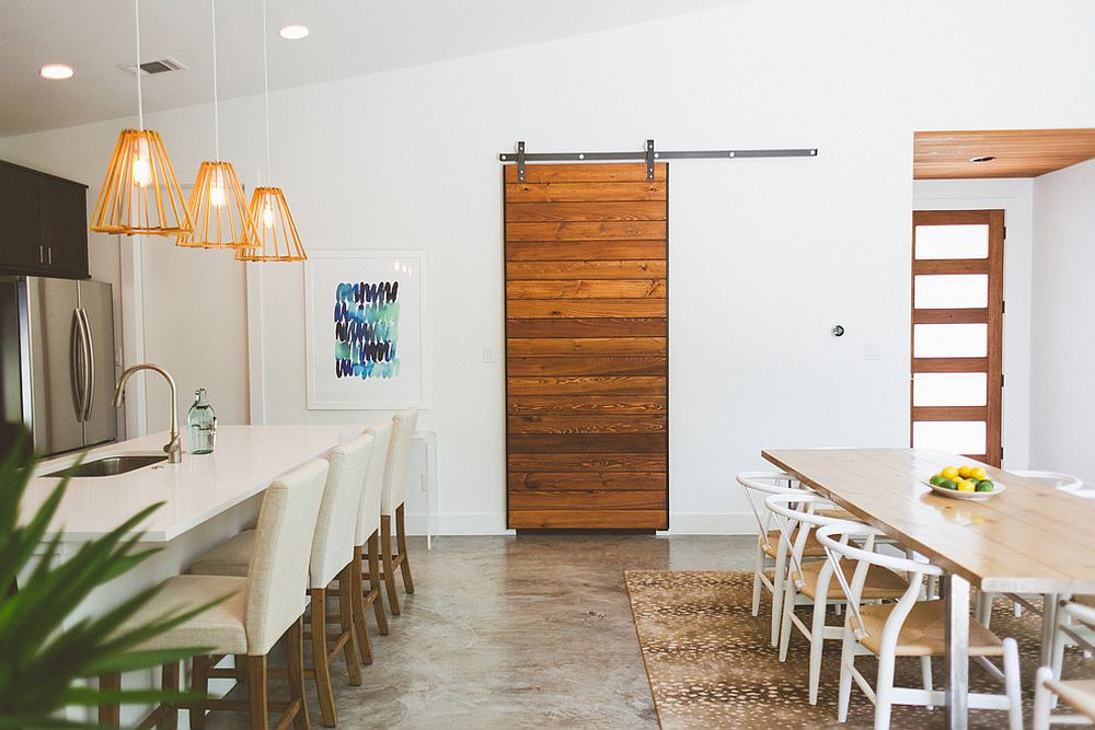 Striking-sliding-barn-door-hides-the-pantry-in-this-kitchen-and-dining-space